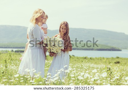 Happy mother playing with her daughter in flower field - stock photo