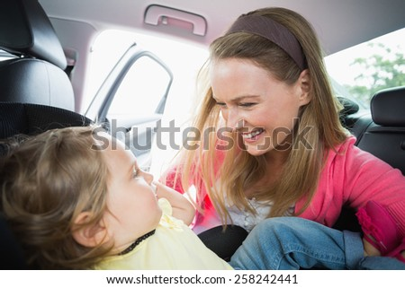 Happy mother playing with her daughter in their car - stock photo
