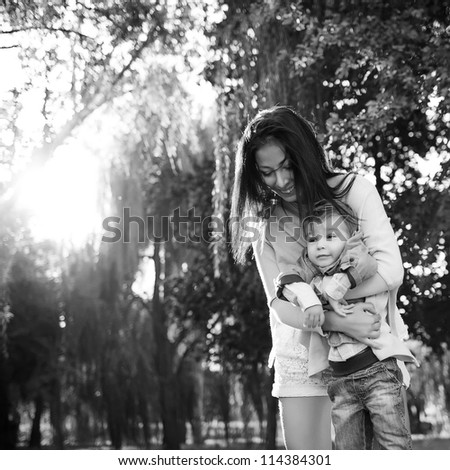happy mother playing with her son in the park,black and white
