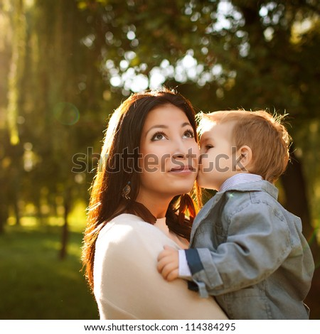 happy mother playing with her son in the park, son kissing his mum - stock photo