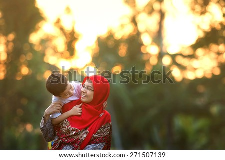 Happy mother playing with her son in the park. Toned image. Selective focus. - stock photo