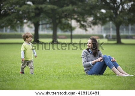 Happy Mother playing with her toddler son outdoors. Love and togetherness concept. - stock photo