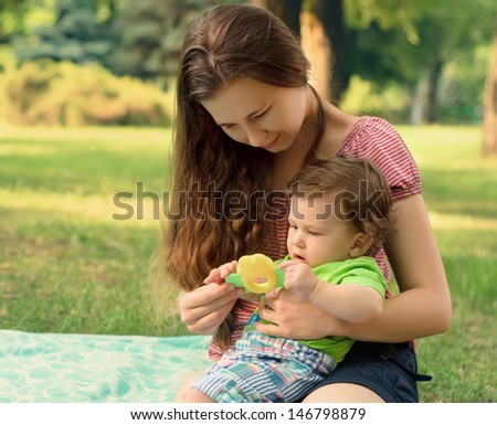 Happy mother playing with his son on lawn in summer park - stock photo