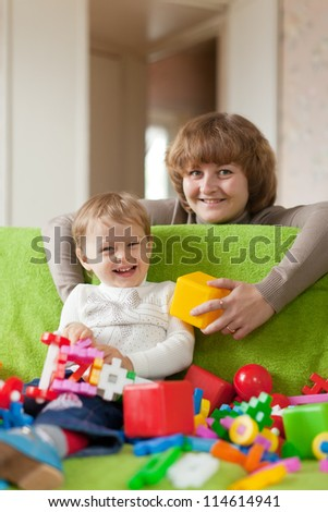 Happy mother plays with child in home interior - stock photo