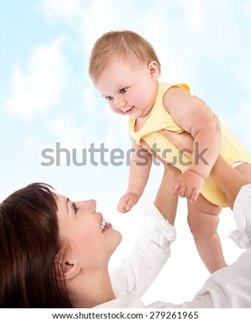 Happy mother plays with her cute little adorable baby, mommy lifting up daughter in the sky, having fun outdoors, love and happiness concept