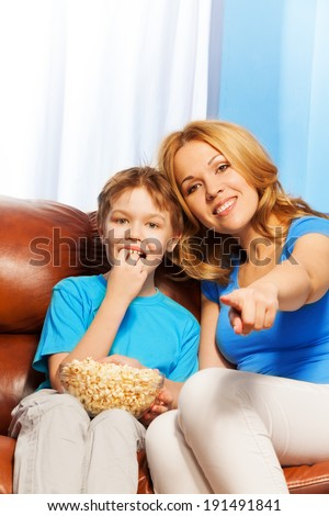 Happy mother pointing forward and son watch TV - stock photo