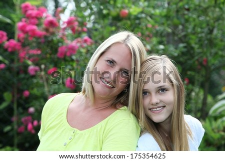 Happy mother posing with her teenage daughter in the garden as the two affectionately nuzzle heads and smile at the camera - stock photo