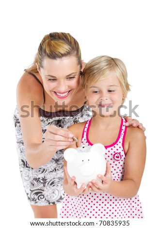 happy mother putting coins into her daughter's piggybank - stock photo