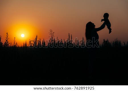 tall grass silhouette. Happy Mother Raises A Child On Her Hands, Sunset In Nature, Tall Grass, Grass Silhouette