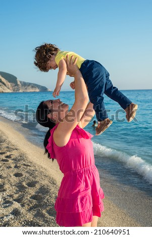 Happy mother raising toddler boy in the sun at sea - stock photo