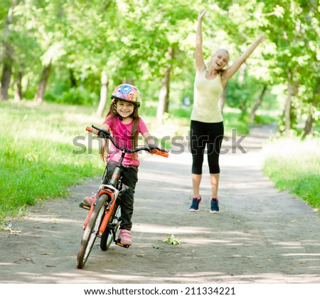 happy mother rejoices that her daughter learned to ride a bike - stock photo