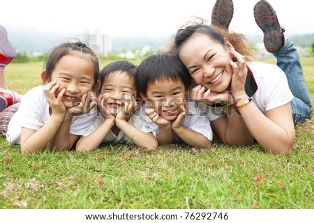 Happy mother's day. asian mother and her children on the green field - stock photo