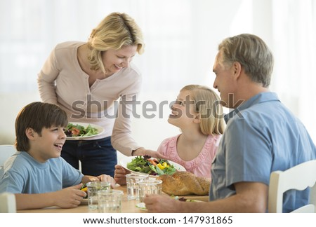 Happy mother serving food to family at dining table - stock photo