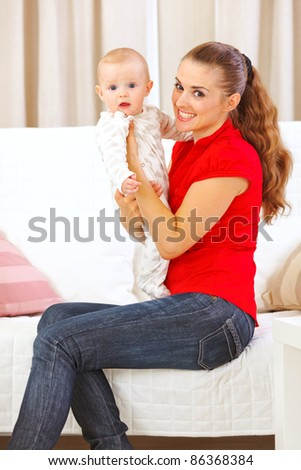 Happy mother sitting on divan and holding adorable baby in hands