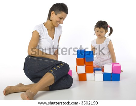 Happy mother sitting on the floor with daughter in front of colored blocks. White background - stock photo