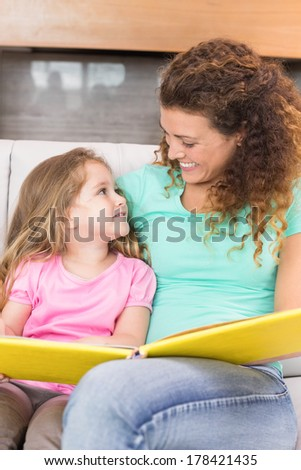 Happy mother sitting with her little daughter reading a storybook at home in living room - stock photo