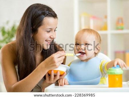Happy mother spoon feeding baby child at home