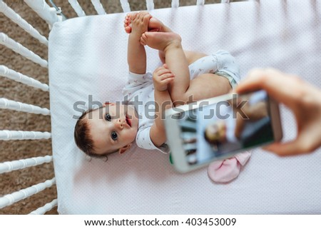 Happy mother taking a picture of her baby girl in crib with smart phone - stock photo