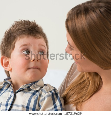 Happy mother talking to her son at home - stock photo