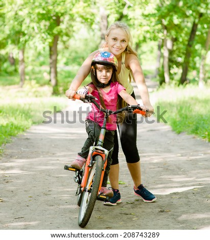 happy mother teaches his daughter to ride a bike - stock photo