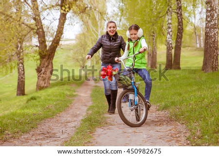 happy mother teaches his daughter to ride a bike. A mother is glad to successes of daughter