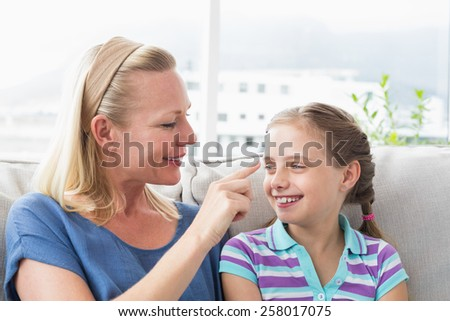 Happy mother touching daughter in living room