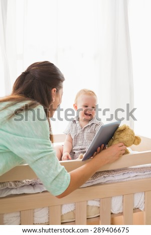 Happy mother using tablet with his baby boy at home in bedroom