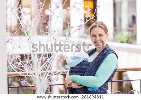 Happy mother walking with her baby in sling in shopping mall - stock photo