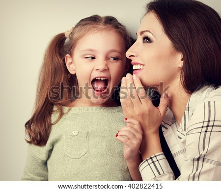 Happy mother whispering the secret to her surprising cute girl in ear on blue background