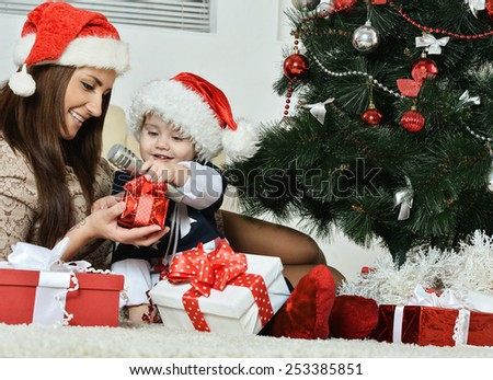 Happy mother with a little boy near a Christmas tree. new year gifts - stock photo