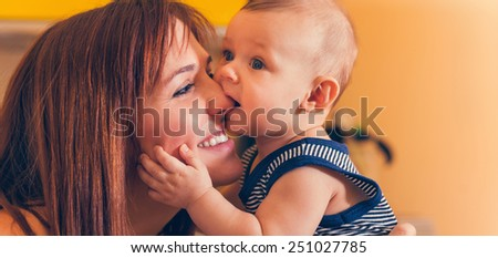 Happy Mother With Adorable Baby Boy In Intimate Embrace - stock photo