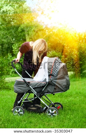 happy mother with baby carriage in city park - stock photo