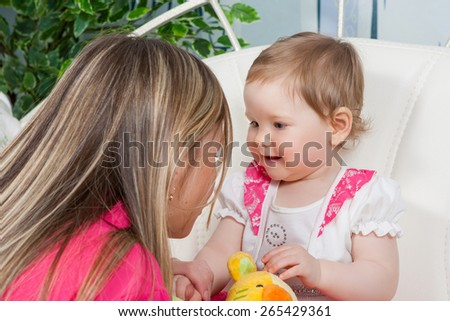 Happy mother with  baby daughter in a beautiful dress at home. Mom tells daughter story. Baby listens with delight. - stock photo