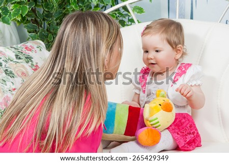 Happy mother with  baby daughter in a beautiful dress at home near the fireplace. Mom tells  story. Child listens delight.