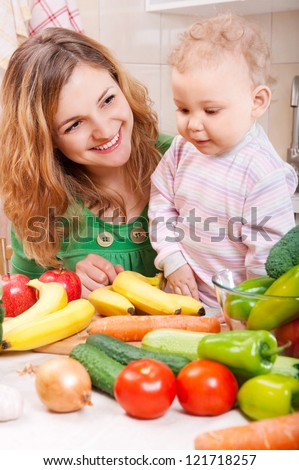Happy mother with baby daughter preparing vegetable salad