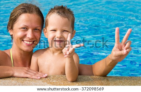 happy mother with baby in swimming pool showing ok sign