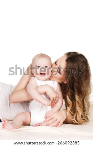 happy mother with baby. joyful mother playing with her baby infant. Happy cheerful family. Mother and baby kissing, laughing and hugging - stock photo