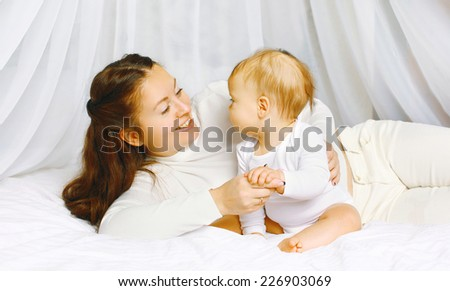 Happy mother with baby on the bed