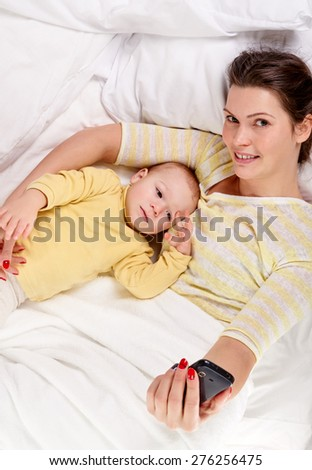 happy mother with baby on white bed and make a selfie, shot from above - stock photo