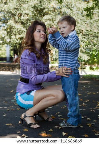 Happy mother with boy in autumn park - stock photo