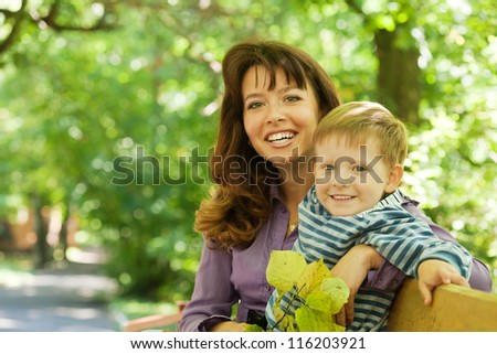 Happy mother with boy on bench in park - stock photo