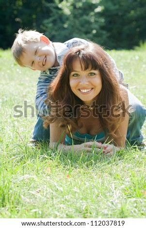 Happy mother with boy on grass in park - stock photo