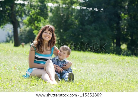 Happy mother with boy sits in grass lawn
