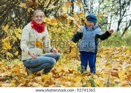 Happy mother with   boy throw up maple leaves in autumn - stock photo