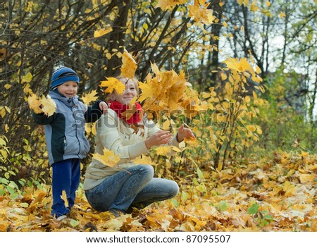 Happy mother with   boy  throwing maple leaves in the air - stock photo