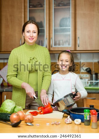 Happy mother with cheerful little daughter cooking together at home kitchen - stock photo