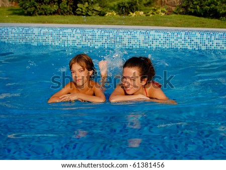 Happy mother with child in swimming pool - stock photo