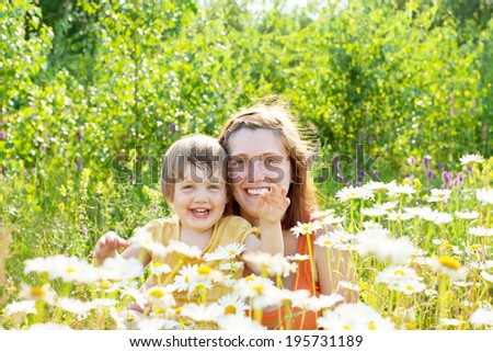 Happy mother with child sits in camomile plant
