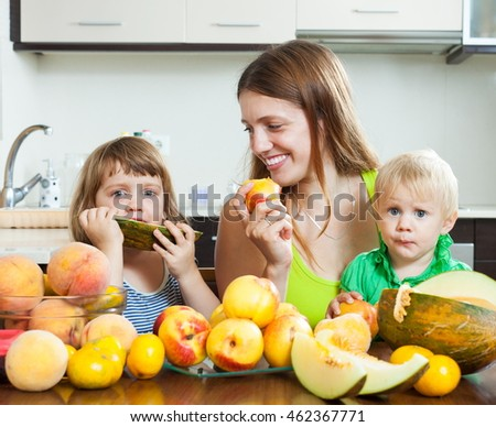 Happy mother with children eating melon and other fruits over  table at home interior