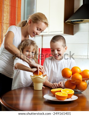 Happy mother with children squeezed orange juice - stock photo
